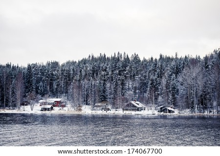Wooden cottage in winter forest covered by snow in Central Finland