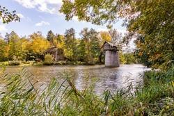 Wooden cottage on abandoned bridge pillar in autumn sunny day