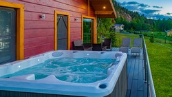 Wooden cottage with veranda for SPA treatments. Hot tub on the balcony of the country house. A place for relaxation. SPA treatments in the fresh air. Cottage on the background of the mountain.