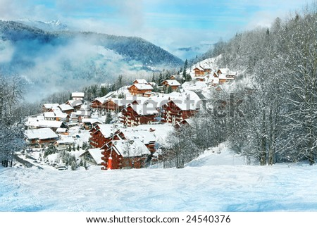 Wooden cottages in the forest covered by snow