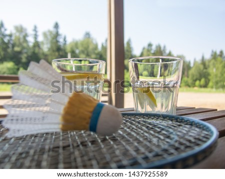 Wooden country furniture on the terrace of a country house. Badminton rackets and shuttlecock on wooden table.Two refreshing drinks with a refreshing lemonade with a slice of lemon in the background.  #1437925589