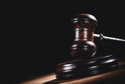 Wooden court gavel on black background. Symbol of justice, judge and trial. Auction.