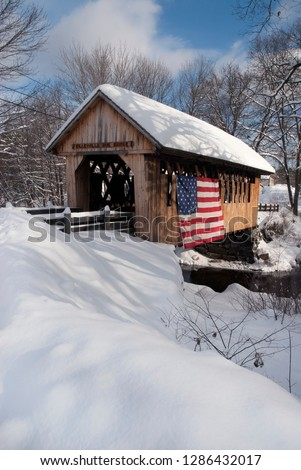 Wooden covered bridge covered in snow displays patriotism with Amercian flag in New England. #1286432017