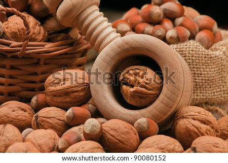 wooden cracker, walnuts and hazel-nuts on the table