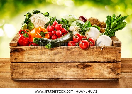 Shutterstock Wooden crate of farm fresh vegetables with cauliflower, tomatoes, zucchini, turnips and colorful sweet bell peppers on a wooden table outdoors in sparkling sunlight on greenery