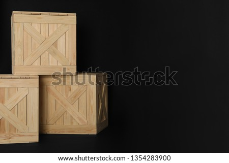 Wooden crates on black background, space for text. Shipping containers #1354283900