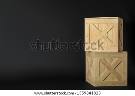 Wooden crates on black background, space for text. Shipping containers #1359841823