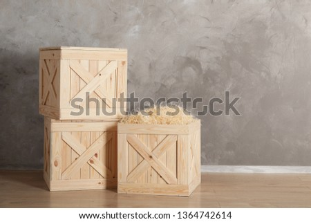 Wooden crates on floor against color background, space for text #1364742614