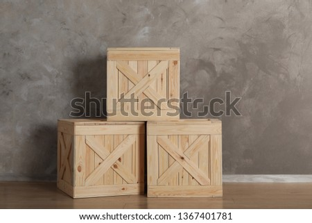 Wooden crates on floor against color background, space for text #1367401781