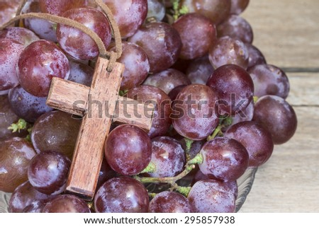 Wooden cross and grape on wooden background, christian symbol Jesus is the true vine from bible verses John 15:1