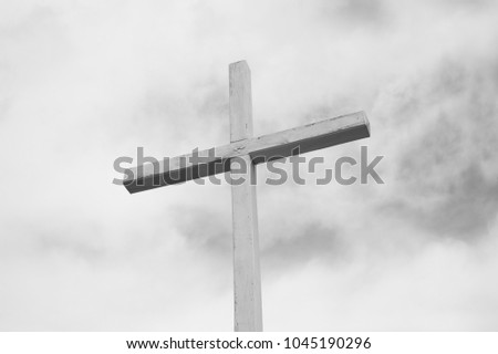 Wooden cross as religious symbol of Christianity and Christian religion - grey cloudy sky in the background. Minimalist symbolism. Low contrast #1045190296