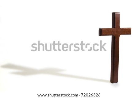 Wooden cross casting a shadow on a white background