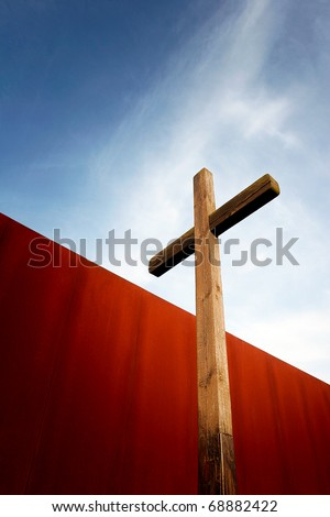 Wooden cross in front of rusty iron wall