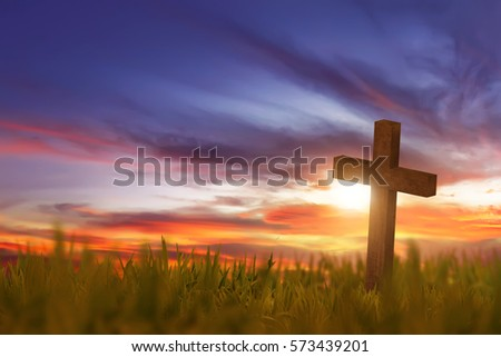 Wooden cross on green grass with sunset in the sky background #573439201