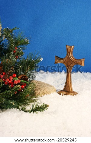 wooden cross, snow, evergreen branch, berries, blue felt background with room for copy