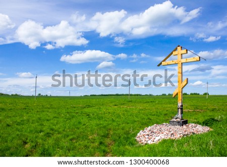 Wooden cross, the symbol of the Christian faith, against the background of a green field and blue sky. White clouds on a blue sky #1300400068