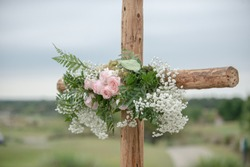 Wooden cross wedding altar with pink roses for outdoor wedding ceremony