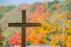 Wooden cross with autumn color trees in background, in a cemetery