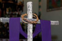 wooden cross with crown of thorns and purple fabric, catholic symbols, time of lent