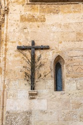 Wooden cross with olive branch next to a Gothic window on the main facade of the Christian church of Sineu, Mallorca island, Spain