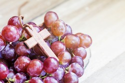 wooden cross with red grape on wooden background, christian concept, Jesus is the true vine from bible verses John 15:1