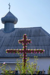 Wooden crucifix decorated with flowers on the background of a Christian church. Religious holiday in Orthodoxy. Small village church. Symbol of faith.