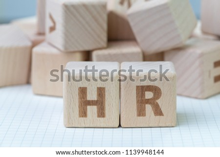 Wooden cube block building the word HR at the center on grid line note book with random other blocks in the background, represent Human Resource department, hiring new job or position in company.