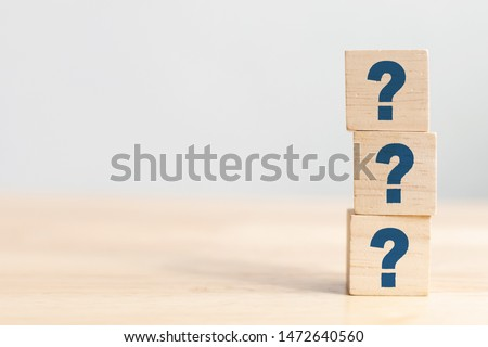 Wooden cube block shape with sign question mark symbol on wood table