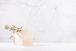 Wooden cube podium with twig of white spring flowers in white and grey marble interior with sun light and shadow. Showcase for cosmetics, products.