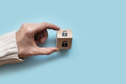 Wooden cube with an open and closed lock pattern. Day of protection of personal data. Protection of personal information