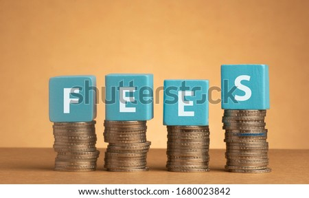 Wooden cube with Fees words on stacked of coins.  Stockfoto ©