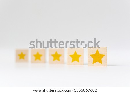 Wooden cube with five star shape on white background. The best excellent business services rating customer experience concept