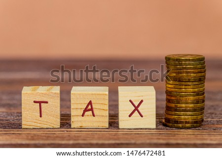 wooden cubes and inscription tax, coins column on the right, the concept of taxation, increase taxes and fees