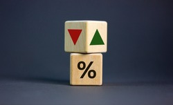 Wooden cubes changes the direction of an arrow symbolizing that the interest rates are going down or vice versa . Business concept. Copy space, beautiful grey background.