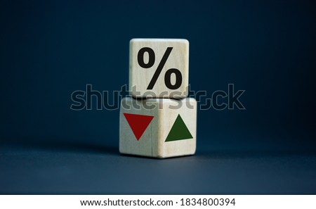 Wooden cubes changes the direction of an arrow symbolizing that the interest rates are going down or vice versa . Business concept. Copy space, beautiful grey background. Foto stock ©