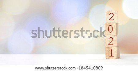 Wooden cubes with 2021 and happy new year over blur bokeh background, banner with copy space for text, new year greeting card template