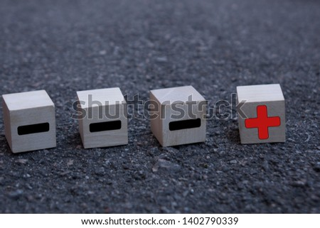 Wooden cubes with drawn plus and minus signs on the dark background, standing out from the crowd concept. #1402790339