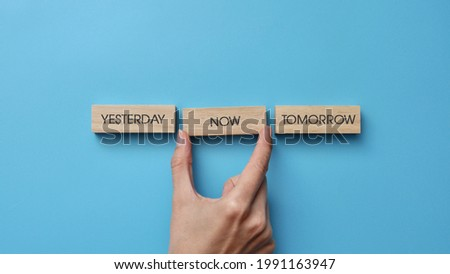 Wooden cubes with inscriptions: yesterday, tomorrow, now. A person's choice of the present moment ストックフォト ©