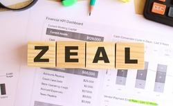 Wooden cubes with letters on the table in the office. Text ZEAL. Financial concept.