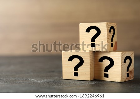 Wooden cubes with question marks on grey stone table, closeup. Space for text