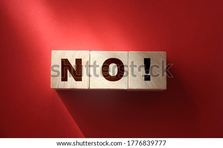 Photo of  Wooden cubes with text no on a red background. Negative answer concept. No risk, no violence or no discrimination concept.