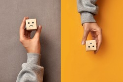 Wooden cubes with the image of a sad and cheerful face. Choosing positive or negative thinking in life