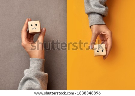 Wooden cubes with the image of a sad and cheerful face. Choosing positive or negative thinking in life Foto stock ©