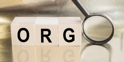 Wooden cubes with the word ORG concept. Magnifying glass with the word on a wooden table. Business concept. Finding an idea.
