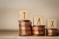 Wooden cubes with the word Tax on money climbing staits, pile of coins ,Tax Concept background closeup