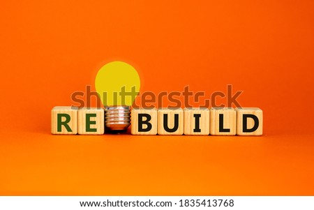 Wooden cubes with word 'rebuild'. Yellow light bulb. Beautiful orange background. Business concept. Copy space. Stockfoto ©