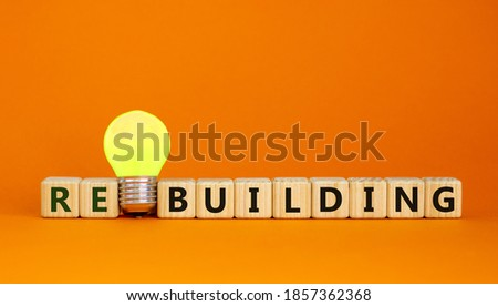 Wooden cubes with word 'rebuilding'. Yellow light bulb. Beautiful orange background. Business concept. Copy space. Stockfoto ©