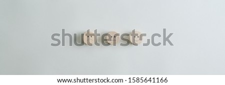 Wooden cut circles with faces representing positive, negative and neutral grade placed in a row over grey background. Wide view image with copy space. Photo stock ©
