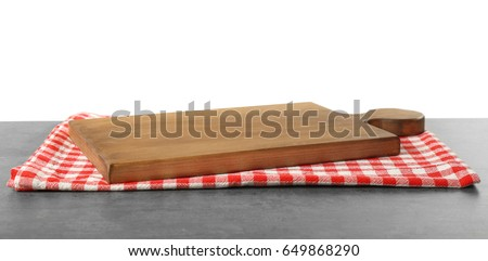 Wooden cutting board and cotton napkin on table #649868290