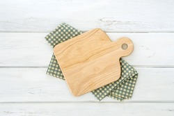 Wooden cutting board on napkin placed on white wooden table ,top view or overhead shot , food menu card or recipes background concept